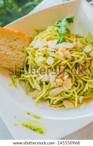Spaghetti with bread in white dish on the stone table