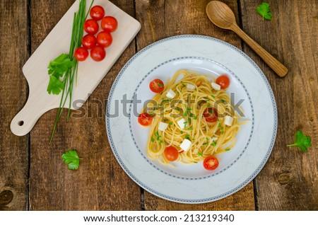 Spaghetti with cherry tomatoes and mozzarella, olive oil - stock photo