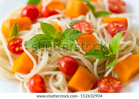 spaghetti with chunks of pumpkin and tomatoes - stock photo