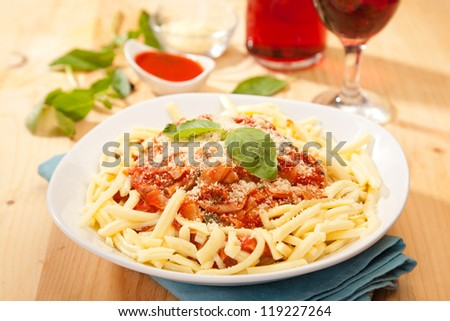 Spaghetti with fresh basil leaves on white dish - stock photo
