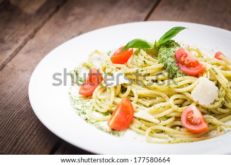 Spaghetti with green pesto, parmesan and cherry tomatoes - stock photo