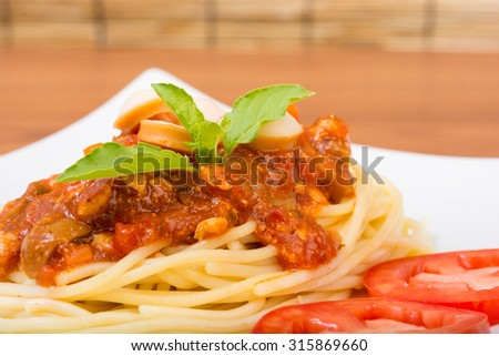 Spaghetti with minced meat and vegetables on wooden background