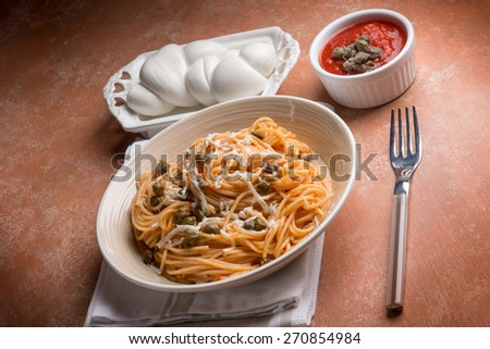 spaghetti with mozzarella tomato and capers - stock photo