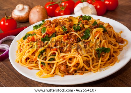 spaghetti with mushroom, vegetables and minced meat in a plate on wooden table