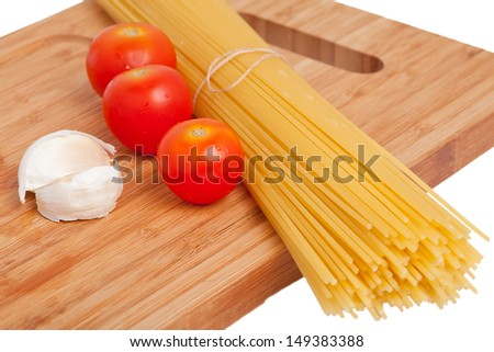 Spaghetti with other ingredients for pasta on a kitchen board isolated
