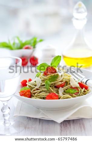 spaghetti with  pesto sauce,cherry tomato and cheese - stock photo
