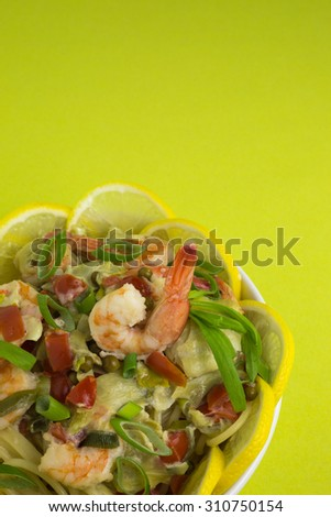 spaghetti with prawns in sherry cream sauce with tomatoes and artichoke decorated with lemon slices and tarragon