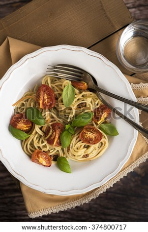 Spaghetti with roasted tomatoes and basil leafs into vintage plate