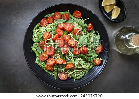 Spaghetti with roasted tomatoes, spinach, and asparagus pesto.  Overhead view food background. - stock photo