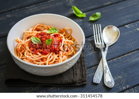 spaghetti with tomato sauce and Basil in a white bowl on a dark wooden surface - stock photo