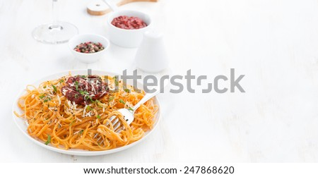 spaghetti with tomato sauce and parmesan on white wooden table, horizontal
