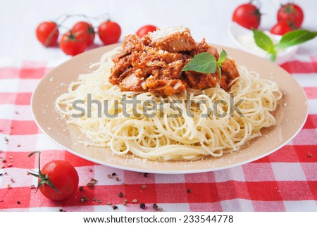 Spaghetti with tomato sauce, meat and fresh basil leaves on white dish - stock photo
