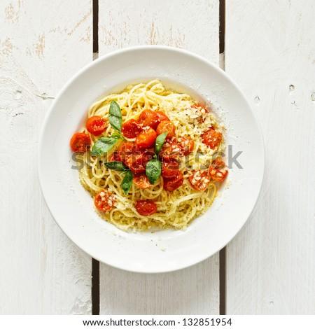 Spaghetti with tomato sauce on white wooden background - stock photo