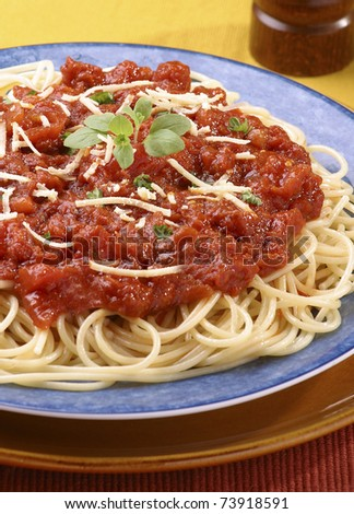 Spaghetti with tomato sauce served on blue plate - stock photo