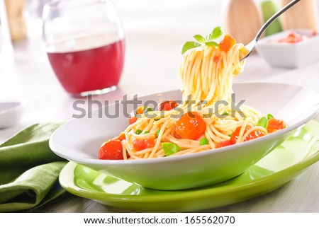 Spaghetti with tomato sauce swirled on a fork garnished with fresh basil leaves
