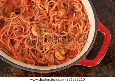 Spaghetti with tomato sauce, vegetables and basil in red Dutch oven on brown rustic background - stock photo