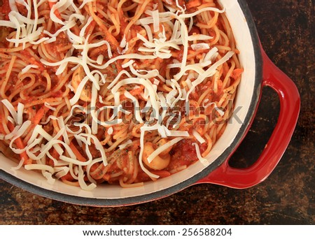 Spaghetti with tomato sauce, vegetables, basil and cheese in red Dutch oven on brown rustic background - stock photo