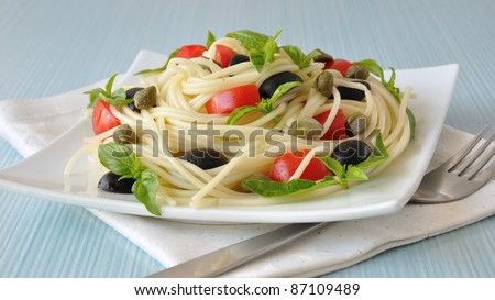 Spaghetti with tomato slices and olives, capers and basil - stock photo
