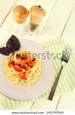 Spaghetti with tomatoes and basil leaves on napkin on wooden background