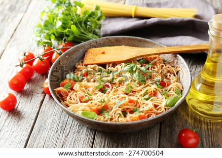 Spaghetti with tomatoes and basil on grey wooden background - stock photo