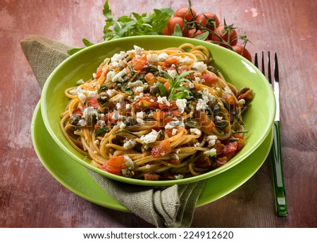 spaghetti with tomatoes cheese capers and arugula - stock photo