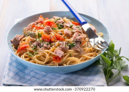 spaghetti with tuna capers and  tomatoes, selective focus - stock photo