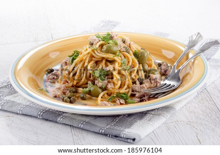 spaghetti with tuna, olive, caper and basil on a plate - stock photo