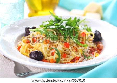 Spaghetti with vegetables and bacon in a sauce of lemon zest and Parmesan cheese decorated with arugula.