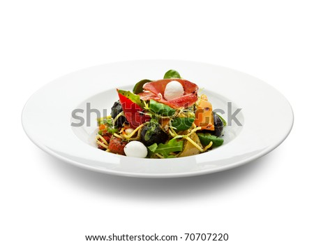 Spaghetti with Vegetables, Ham, Black Olives, Rucola and Pesto Sauce - stock photo