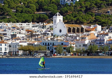 Spain coastal village in the Mediterranean with a windsurfer in foreground, Puerto de la Selva ,Costa Brava, Catalonia, Spain