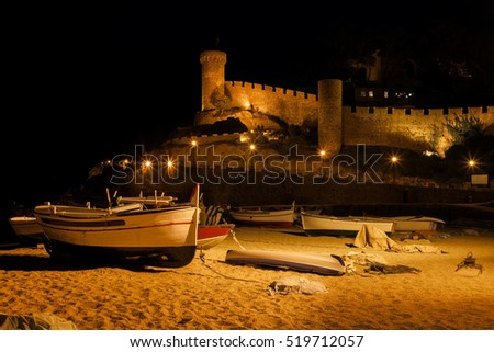 Spain, Costa Brava, Tossa de Mar Castle at night, medieval wall of the Old Town from the beach with fishing boats