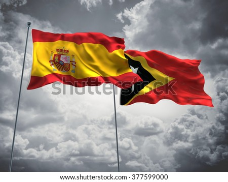 Spain & East Timor Flags are waving in the sky with dark clouds