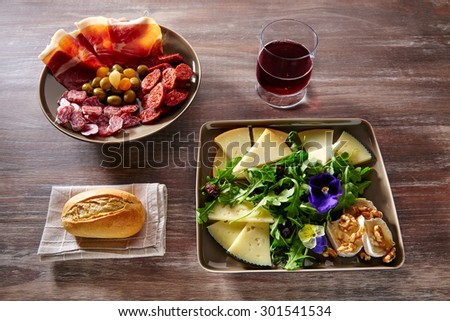 Spain food tapas ham sausage and salad with cheese honey and nuts - stock photo
