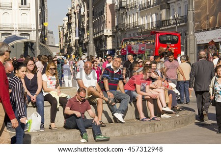 Spain,Madrid - May 27, 2016: People sit on the bench of a fountain in the Puerta del Sol square in Madrid, Spain on May 27, 2016 - stock photo