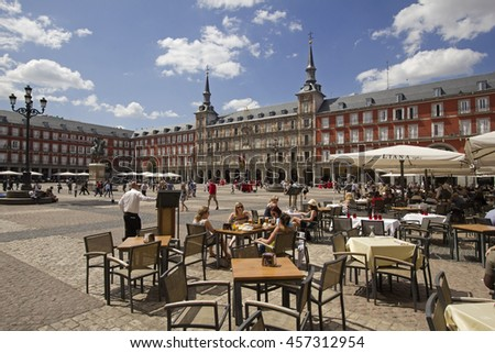 Spain,Madrid - May 27, 2016: Tourists sit at tables of a restaurant in the Plaza Mayor city square in Madrid, Spain on May 27, 2016 - stock photo