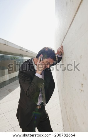 Spain, Mallorca, Businessman using mobile phone, leaning against wall - stock photo