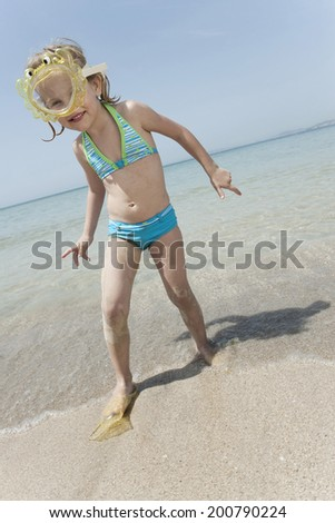 Spain, Mallorca, cute little girl on the beach wearing diving goggles - stock photo