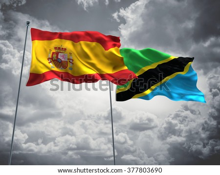 Spain & Tanzania Flags are waving in the sky with dark clouds