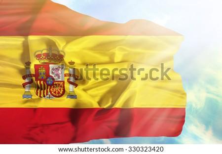 Spain waving flag against blue sky with sunrays - stock photo