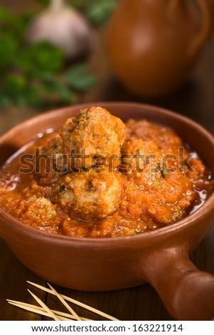 Spanish albondigas (meatballs) in tomato sauce in rustic bowl with toothpick in the front (Selective Focus, Focus on the meatball on the top) - stock photo