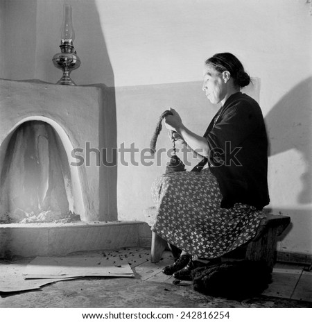 Spanish-American women, Maclovia Lopez, hand spinning wool by the light of the fire in New Mexico's Taos County. New Mexico has a four century tradition of wool production and weaving. - stock photo