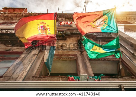 Spanish and Portuguese flags hanging on a building in Porto - stock photo