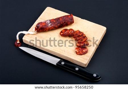 Spanish chorizo sausage on rustic board - stock photo