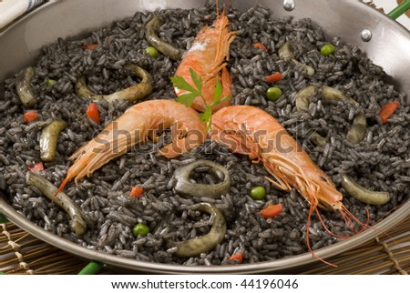 Spanish cuisine. Arroz negro. Black rice cooked in squid ink. Served in a typical paellera. - stock photo