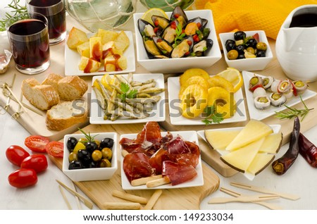 Spanish cuisine. Assortment of  Tapas including Serrano Ham, Manchego Cheese, Marinated Olives, Pikles, Potatoes in Hot Sauce, and others, served with red wine. - stock photo