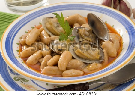 Spanish Cuisine. Fabes con almejas. Asturian clams and beans. Selective focus. white background.
