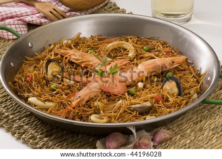 Spanish cuisine. Fideua. Seafood spaghetti cooked in a typical paellera.