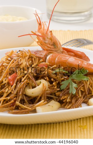 Spanish cuisine. Fideua. Seafood spaghetti served with garlic mayonnaise sauce. White background.