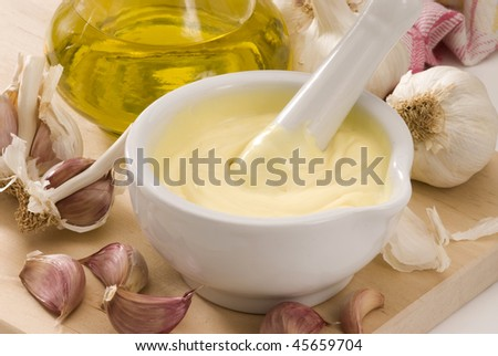 Spanish cuisine. Garlic mayonnaise sauce in a white mortar. Selective focus.Alioli.