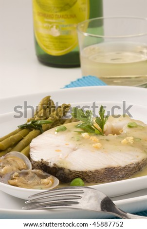 Spanish cuisine. Hake Basque style. Txacoli wine in background. Selective focus. Merluza en salsa verde. - stock photo